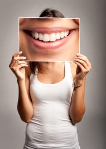 young woman in white tank top holding up a photograph of a smile in front of her face