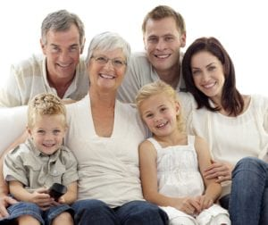 family of grandparents, parents, and children smiling and watching tv at home