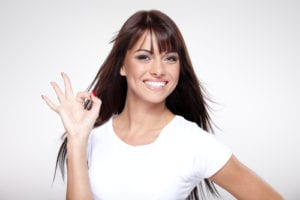portrait of young woman smiling and giving the OK sign