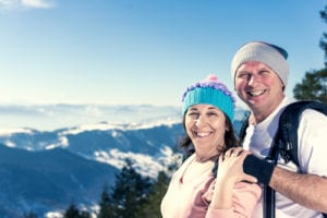 photograph of man and woman dressed in winter gear and smiling with mountains in the background