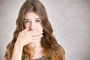 young woman covering her mouth, embarrassed of her bad breath