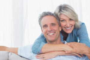 middle-aged couple hugging and smiling in front of white background