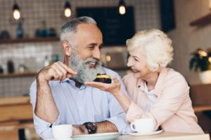 an older couple enjoying coffee and dessert at a cafe