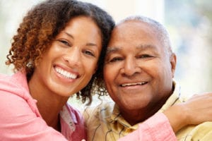 up close photograph of smiling African American man and his daughter