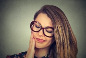 young woman in glasses in pain with a toothache