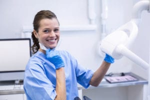 portrait of a dental hygienist ready to perform a dental cleaning