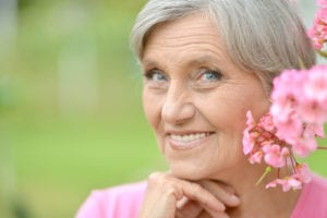 smiling older woman dressed in pink outside
