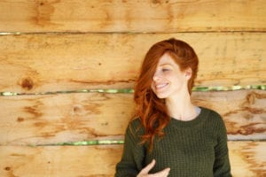 portrait of young redheaded woman smiling in front of wooden background