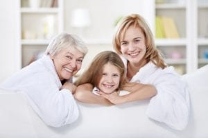portrait of three generations of women smiling at home