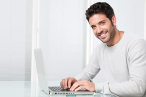 portrait of smiling man working on laptop