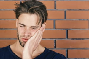 young man suffering from jaw pain due to TMJ issues or teeth grinding