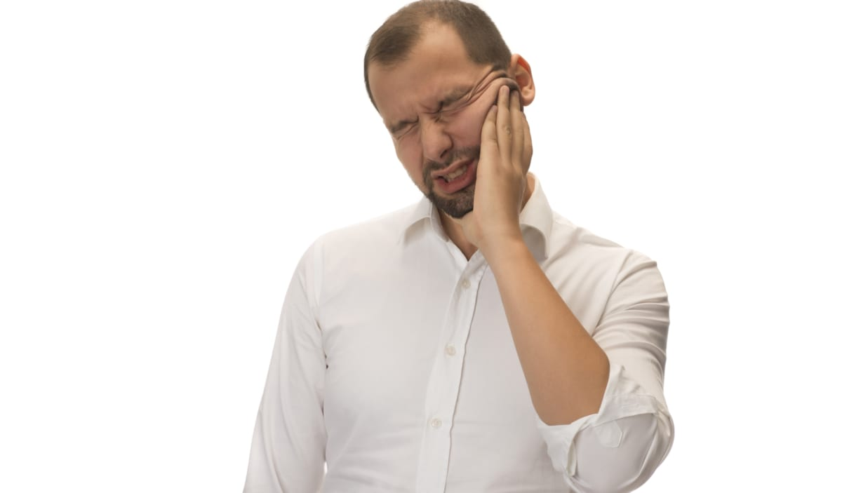 man in white shirt with painful toothache