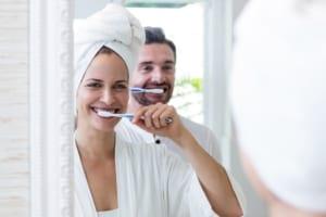 happy man and woman brushing teeth in the bathroom