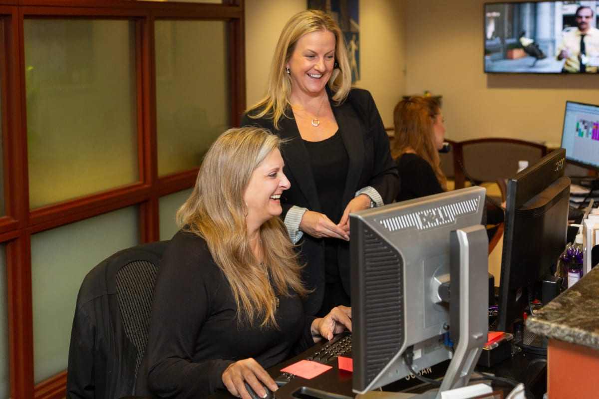 co workers enjoying teamwork at the receptionists desk
