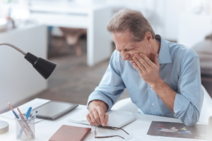 older man at desk wincing due to tooth pain